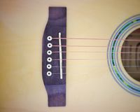 Vintage phto of acoustic guitar strings on wooden table in the room, close up top view and sunlight with empty space for you text. Vintage phto of acoustic royalty free stock image