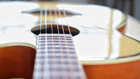 Acoustic guitar strings on wooden table in the room, close up top view and sunlight with empty space for you text. Vintage phto of acoustic guitar strings on royalty free stock images