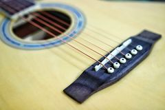 Acoustic guitar strings on wooden table in the room, close up top view and sunlight with empty space for you text. Vintage phto of acoustic guitar strings on stock photo