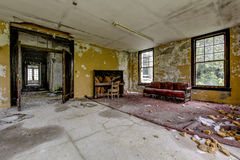 Vintage Piano and Couch - Abandoned Hospital / Sanitarium - New York. An interior view of a vintage piano and couch inside an abandoned hospital in New York royalty free stock images