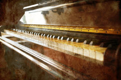 Vintage piano on grunge. Close view to a vintage piano keyboard on a grunge background stock images