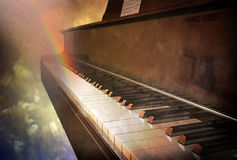 Vintage piano keyboard. Image of a piano keyboard on a vintage background. A rainbow is created by notes coming out from the keys Royalty Free Stock Photography