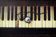 Vintage piano keys with antique pocket watch with a chain – time concept. Royalty Free Stock Photo