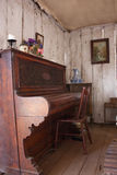 Vintage piano in old wooden cottage. Hand carved old fashioned piano set in a colonial wooden cottage with bare floorboards Royalty Free Stock Images