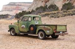 Vintage Pick-Up Truck. The left-side rear view of an old rusty Chevrolet 3600 Pick-up covered with chipped green paint standing at the foot of a mountain Stock Photography