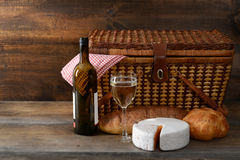 Vintage picnic basket with wine. And cheese on old wood royalty free stock image
