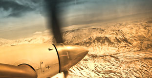 Vintage picture - Airplane fly over mountains Stock Photography