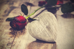 Vintage picture of heart on a wooden background with red rose. Stock Photos