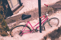 Vintage picture of a pink bike covered in snow during snow storm. In Montreal royalty free stock images