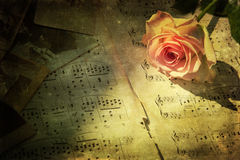 Vintage picture of a pink rose with music notes. Vintage textured picture of a pink rose and old photographs on old sheets of music Stock Image