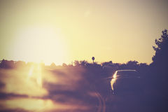 Vintage picture of road with cars in motion against sun. Stock Image