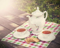 Vintage picture of tea cups and teapot on wooden t Royalty Free Stock Image