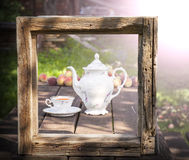 Vintage picture of tea set in garden in wooden frame. Stock Photo