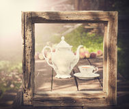 Vintage picture of tea set in garden in wooden frame. Stock Photos