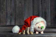 Vintage Piggy Bank with Santa Claus hat stock photos