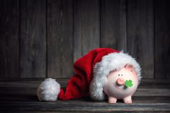 Vintage Piggy Bank with Santa Claus hat stock images