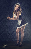 Vintage pin up maid's uniform, holding a broom Royalty Free Stock Photography