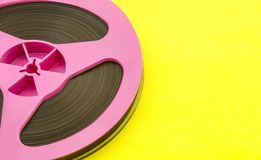 Vintage pink audio reel with recording tape on yellow paper background. Trendy pop art style. stock images