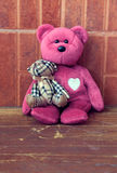 Vintage pink bear toy alone on wooden backgrounds Stock Photo
