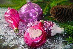 Vintage pink Christmas decorations on a background of Christmas. Tree branches. Christmas balls in the shape in the form of cones and hearts Royalty Free Stock Images