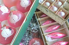 Vintage pink Christmas tree decorations in boxes piled on a table. Vintage frosted pink Christmas tree decorations in boxes piled on a table Stock Photo