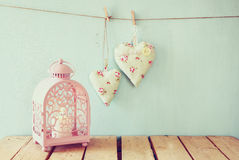 Vintage pink classical frame, fabric hearts hanging on the rope and lantern with garland lights, on wooden table Royalty Free Stock Images
