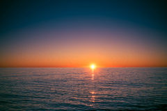 Illustration of a bright sunset over the dark sea. Illustration of a bright sunset over the dark calm sea Stock Photography