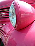 Vintage Pink Hot Rod & Headlight. Partial view of a pink hot rod with reflection of another car Royalty Free Stock Image