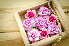 Vintage pink rose and Pearl Necklace on wooden background. Royalty Free Stock Image