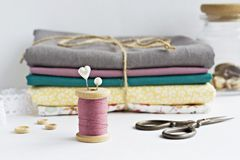Vintage thread spool, pins, wooden buttons, scissors and fabrics royalty free stock image
