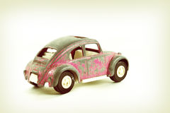 Vintage Pink Toy Car. Pink vintage toy car from the 60's emulating a popular German vehicle of the time Stock Photo