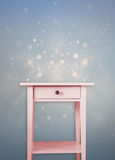 Vintage pink wooden chest drawer near vintage  dreamy blue glitter background Royalty Free Stock Photography