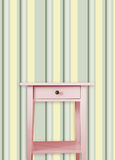 Vintage pink wooden chest drawer near vintage stripes wall Stock Photos