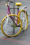 Vintage pink and yellow bike on the street Stock Images