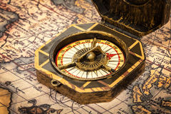 Vintage pirate compass on ancient map. Vintage pirate retro compass close up on ancient world map royalty free stock image