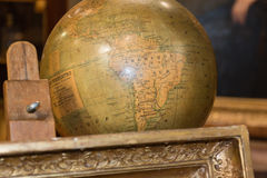 Vintage plastic globe beyond antique frame Stock Photography