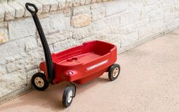 Red Radio Flyer wagon against a stone wall. Vintage plastic red Radio Flyer wagon against a limestone block wall Stock Photography