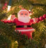 Vintage Plastic Santa Ornament. Close up of a vintage plastic Santa ornament wearing a red suit with pine branch, needles and lights in the background Royalty Free Stock Photo