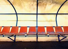 Vintage plastic seats on outdoor stadium players bench, chairs with worn paint below yellow roof. Stock Photography