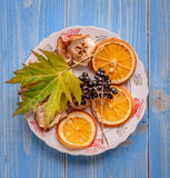 Vintage plate with chips of orange and pear. Leaf of maple and mountain ash. on vintage wooden desk. Autumn concept Stock Images