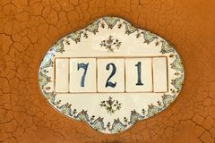 Plate with house number with mud wall. stock image