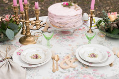 Vintage plates with roses on a table with cutlery and glasses. Pink cake with rose Royalty Free Stock Images