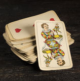 Vintage playing card. Stack of old playing cards with joker in the foreground Stock Images