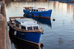 Vintage pleasure boats. Moored vintage pleasure boats at the granite wall of the river channel stock photos