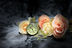Vintage pocket clock with rose flower on black fabric background. Love of time concept. still life style.  royalty free stock photos