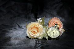 Vintage pocket clock with rose flower on black fabric background. Love of time concept. still life style royalty free stock photo