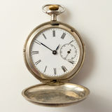 Vintage pocket watch. Vintage pocket watch close up on a light plane Royalty Free Stock Image