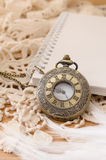 Vintage pocket watch with blank note book on lace background Stock Photography