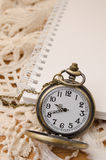 Vintage pocket watch with blank note book on lace background Royalty Free Stock Images