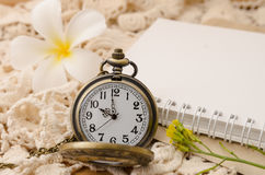 Vintage pocket watch with blank note book on lace background Royalty Free Stock Photography